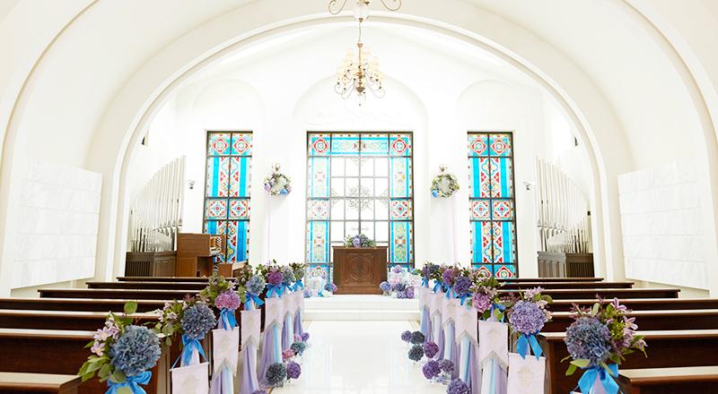白く輝く大理石のバージンロードとステンドグラス 越しの色鮮やかな光に包まれた温かな空間