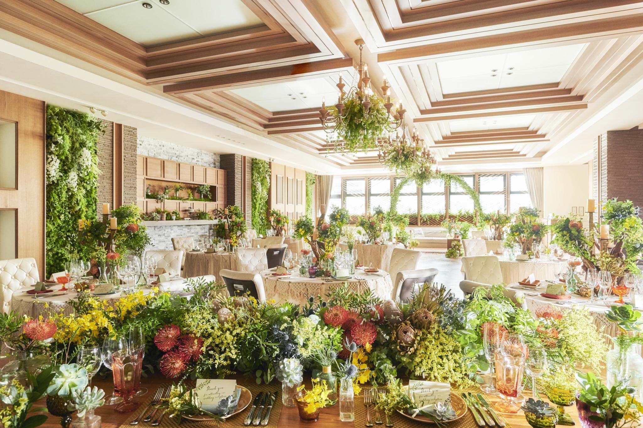 木の質感ときらめくシャンデリアの洗練されたデザインが印象的な 上質で優しい雰囲気のパーティ会場