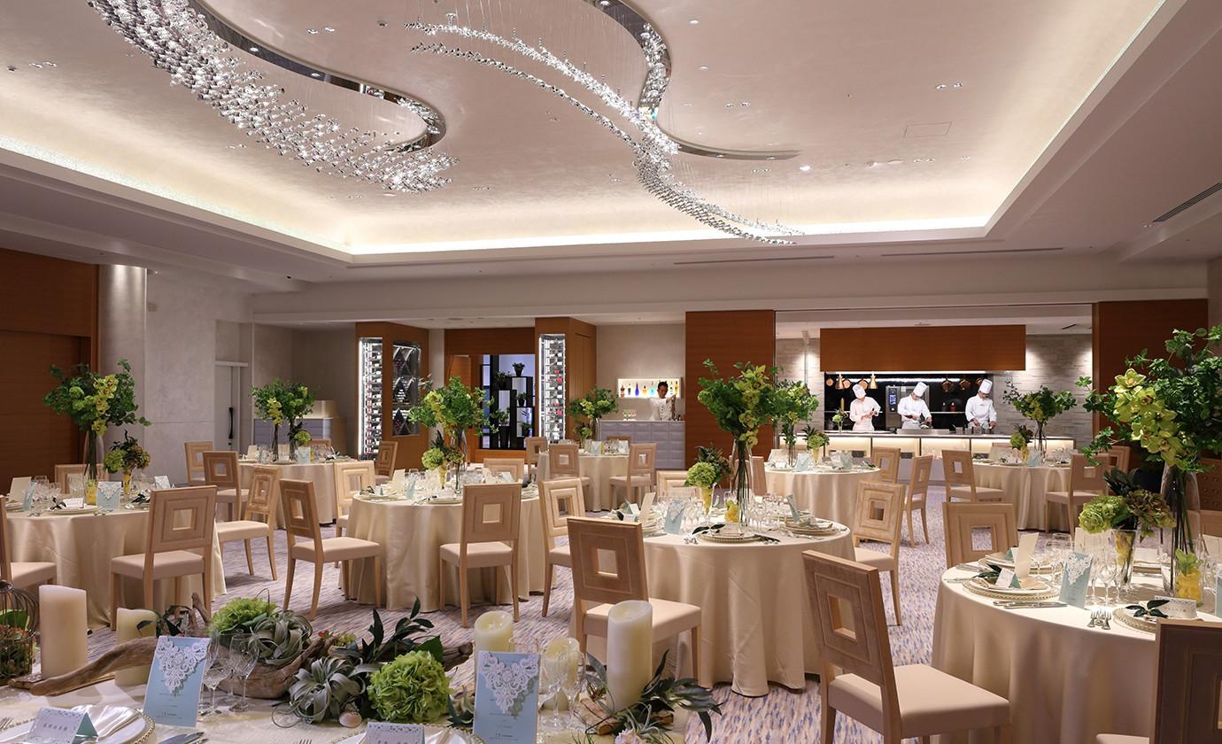 白を基調とした開放的で上質な空間。天井には、おふたりの出会いからご結婚を二本の水波で表現したシャンデリアが、祝福するかのようにきらきらと輝いています
